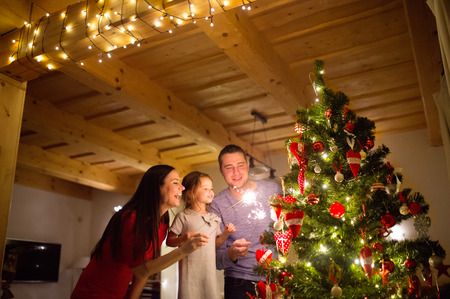 Beautiful young family with little daughter with sparklers at Christmas tree at home.