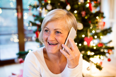 house call: Beautiful senior woman holding smart phone, making phone call, sitting in front of illuminated Christmas tree inside in her house.