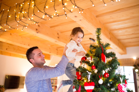 home decorating: Young father holding his little daughter in his arms at home decorating Christmas tree together. Stock Photo