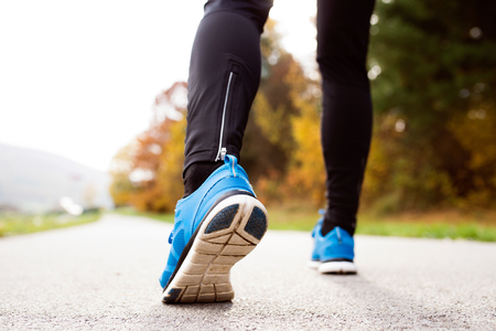 sportsmen: Legs of unrecognizable runner standing on concrete path wearing blue sports shoes, close up.