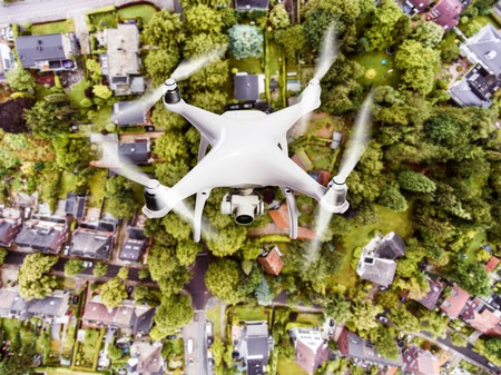 in the suburbs: Hovering drone taking pictures of Dutch town, houses with gardens, green park with trees. Aerial view.