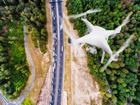 Hovering drone taking pictures of highway junction in the middle of green forest, traffic jam, Netherlands. Aerial view.
