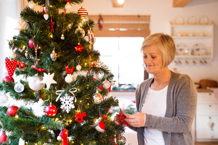 red cardigan: Beautiful senior woman decorating Christmas tree inside in her house.