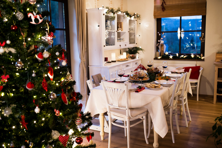 christmas meal: Christmas meal laid on table in decorated dining room. Roasted turkey or chicken, cookies, Christmas tree, plates and glasses of red wine. Stock Photo