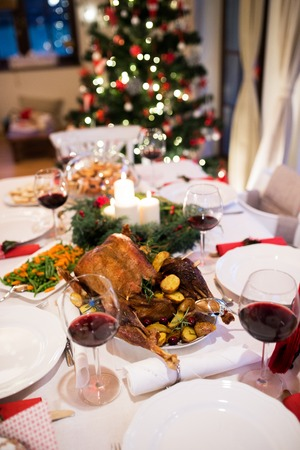 Christmas meal laid on table in decorated dining room. Roasted turkey or chicken, vegetables, cookies, Christmas tree, plates and glasses of red wine.