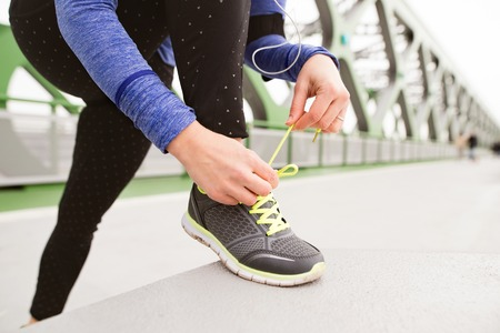 bratislava: Unrecognizable runner in the city tying shoelaces on green steel bridge. Close up. Stock Photo