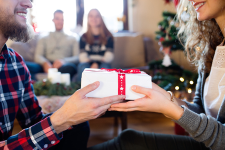 Young friends at decorated Christmas tree celebrating Christmas together exchanging gifts. Unrecognizable hipster man giving gift to beautiful young woman. Stock Photo