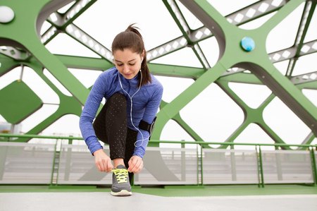 crosscountry: Beutiful runner in the city with earphones, listening music, tying shoelaces on green steel bridge. Close up.