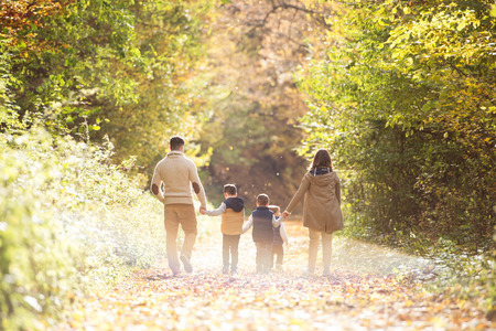 family outside: Beautiful young family on a walk in forest. Mother and father with their three sons in warm clothes outside in colorful autumn nature. Rear view.
