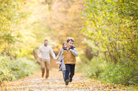 Beautiful young family on a walk in forest. Mother and father with their three sons in warm clothes outside in colorful autumn nature. Stock Photo