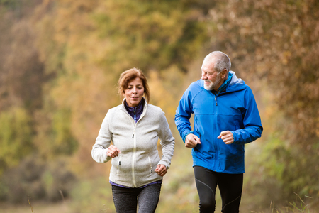 Beautiful active senior couple running together outside in sunny autumn forest Stock Photo