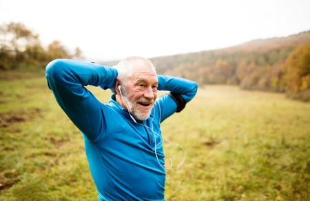 Senior runner in sunny autumn nature doing stretching. Man with earphones, listening music, armband on his arm. Rear view. Stock Photo