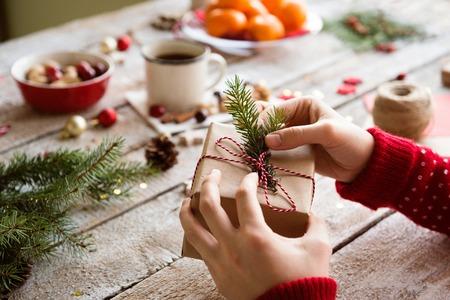 ラッピングとクリスマス プレゼント木製テーブルの背景を飾る認識できない女性の手。スタジオ撮影します。