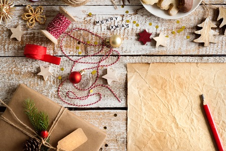 christmas objects: Christmas composition. Empty old sheet of paper. Christmas present and ornaments. Various objects laid on table. Studio shot, wooden background. Copy space. Stock Photo