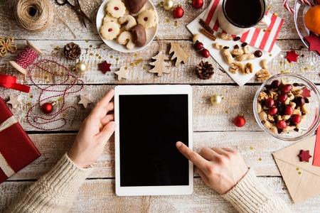 Vánoční kompozice. Ruce nepoznatelného člověka, který drží tabletu. Různé předměty položené na stole. Studio shot, dřevěné pozadí. Kopírovat prostor.