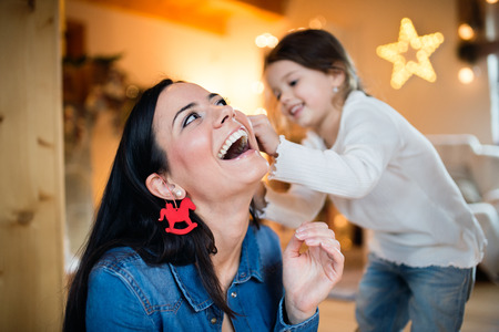Beautiful young mother with little daughter at home decorating Christmas tree together. Little girl giving her mom Christmas ornaments on her ears.