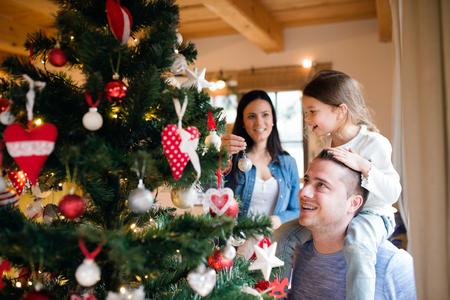 decorating christmas tree: Beautiful young family with little girl decorating Christmas tree at home. Father giving daughter piggyback.