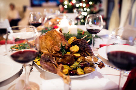 laid: Christmas meal laid on table in decorated dining room. Roasted turkey or chicken, vegetables, Christmas wreath, glass of red wine.