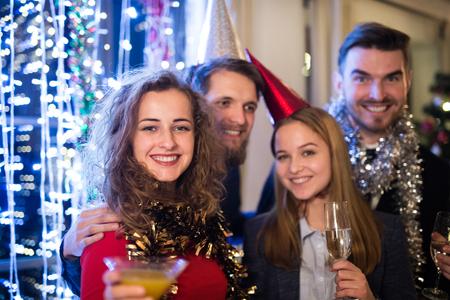 Grupo de amigos que celebran el final del año, que tienen fiesta en Nochevieja, copas de champán.