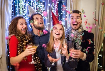 Grupo de amigos que comemoram o fim do ano, tendo partido em New Years Eve, segurando copos de champanhe.