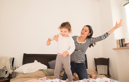 Beautiful young mother having fun with her daughter on bed in her bedroom Stock Photo