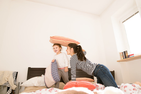 kids having fun: Beautiful young mother having fun with her cute little daughter on bed in her bedroom, playing with pillows