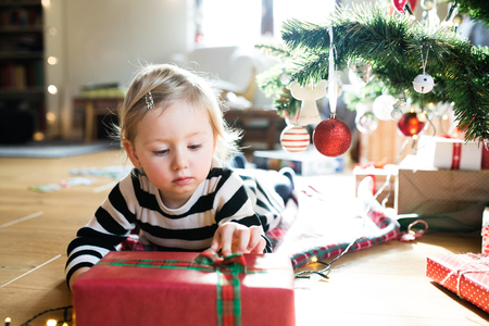 ball and chain: Beautiful little girl lying under the Christmas tree opening her Christmas present. Stock Photo