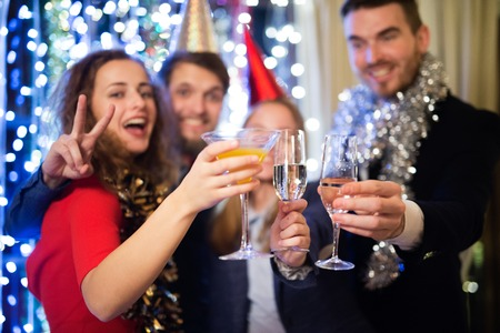 the end of the year: Group of friends celebrating the end of the year, having party on New Years Eve, clinking with champagne. Stock Photo