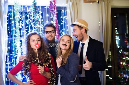 Mooie hipster vrienden met photobooth rekwisieten vieren het einde van het jaar, met feest op New Years Eve, ketting van lichten achter hen. Stockfoto