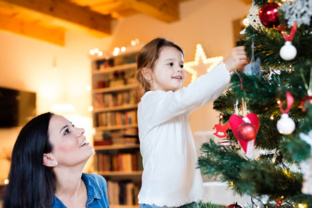 home decorating: Beautiful young mother with little daughter at home decorating Christmas tree together. Stock Photo