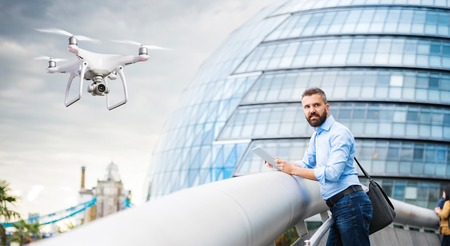 Hovering drone taking pictures of handsome young man with tablet in front of Town Hall in London, England.