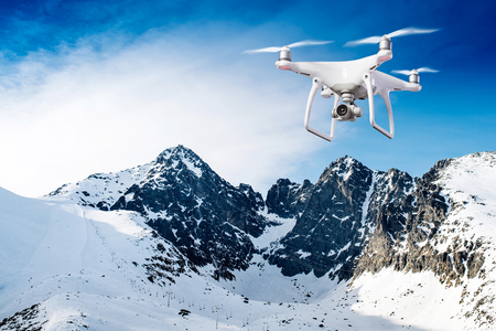 Hovering drone taking pictures of snowy white winter mountains on sunny day with blue sky