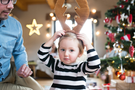 Young father with his cute little daughter at the Christmas tree, wearing brown reindeer antlers.