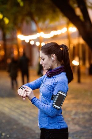light to dark: Beautiful young woman in the town in the evening with smart phone, smartwatch and earphones, listening music. Using a fitness app for tracking weight loss progress, running goal or summary of her run. Stock Photo