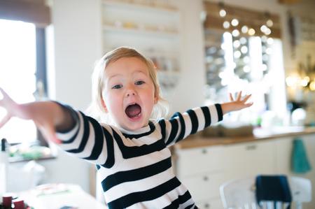 Leuk weinig blond meisje in gestreepte jurk zittend op de keukentafel, schreeuwen, armen gestrekt. Kerst seizoen.