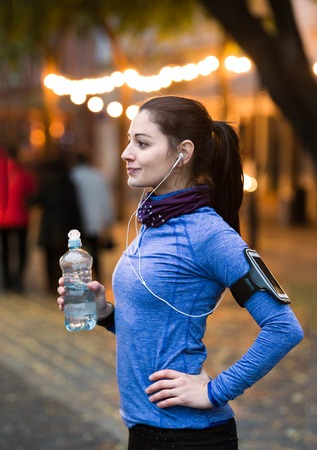 water town: Beautiful young woman with smart phone and earphones, listening music, resting, drinking water from bottle. Running in the illuminated night town. Stock Photo
