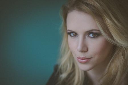 rubia: Cerca de retrato de un modelo de mujer joven rubia con frescos profesional diaria maquillaje sobre un fondo verde.