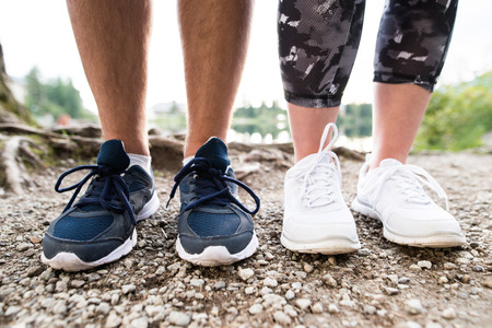 healthy path: Legs of unrecognizable running couple in sports shoes on rocky path. Close up.