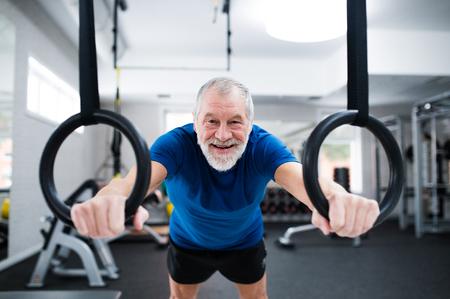 persona de la tercera edad: Hombre mayor en ropa deportiva en el gimnasio que se resuelve en los anillos gimnásticos. Cerca de las manos. Foto de archivo