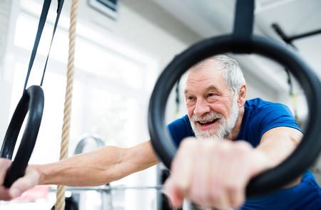 close out: Senior man in sports clothing in gym working out on gymnastic rings. Close up of hands.