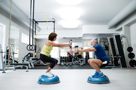Beautiful fit senior couple in gym working out with weights and squatting at the same time Stok Fotoğraf
