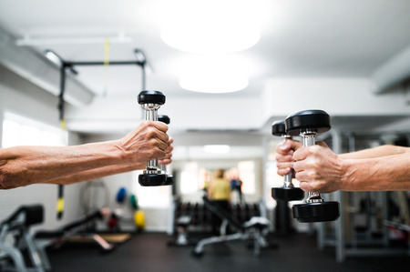 close out: Close up of hands of senior couple in gym working out with weights