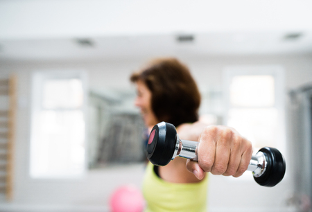 close out: Senior woman in sports clothing in gym working out with weights. Close up of hands.