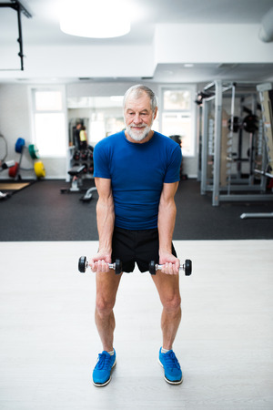 senior men: Senior man in sports clothing in gym working out with weights Stock Photo