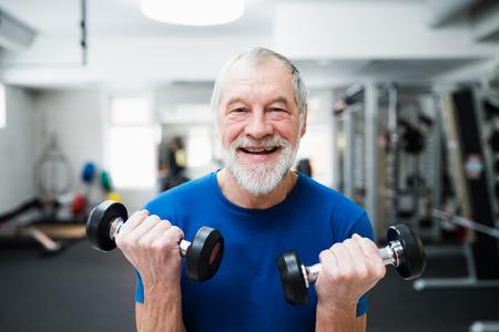 Hogere mens in sportkleding in de sportschool uit te werken met gewichten.
