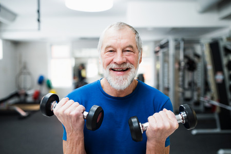 Senior man in sports clothing in gym working out with weights.