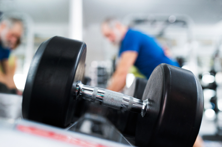 Close up of dumpbell, senior couple in gym working out