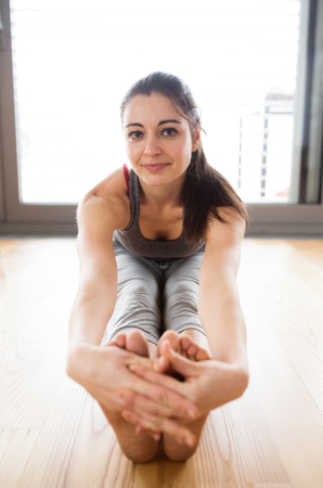 feet soles: Young woman exercising at home, stretching legs. Stock Photo