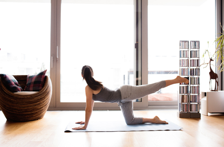 Beautiful young woman exercising at home on mat.