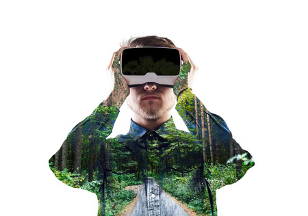 double game: Double exposure. Man wearing virtual reality goggles. Forest. Tr Stock Photo